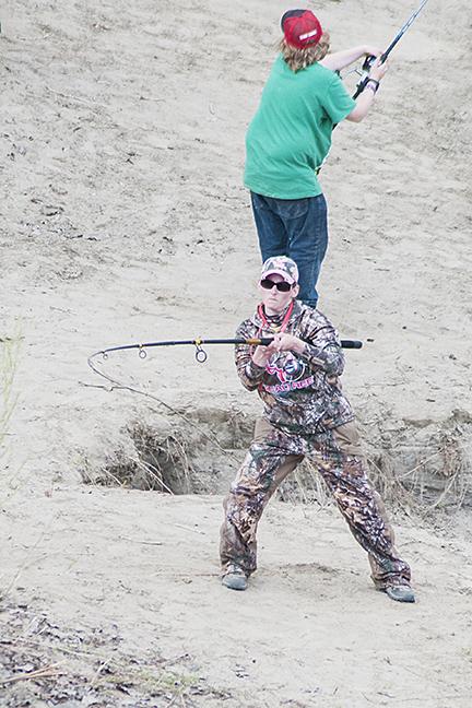 Woman in pink reels in heavy line.