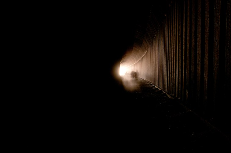 A small bit of light from the end of the tunnel barely illuminates people coming in to the tunnel.