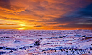 Blaze orange sunset and cold blue snow, badlands and sentinel butte on the horizon.