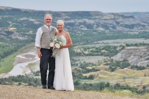 Wedding couple stand on a ridge at the Overlook at the North Unit of the Theodore Roosevelt National Park with the Little Missouri River below.