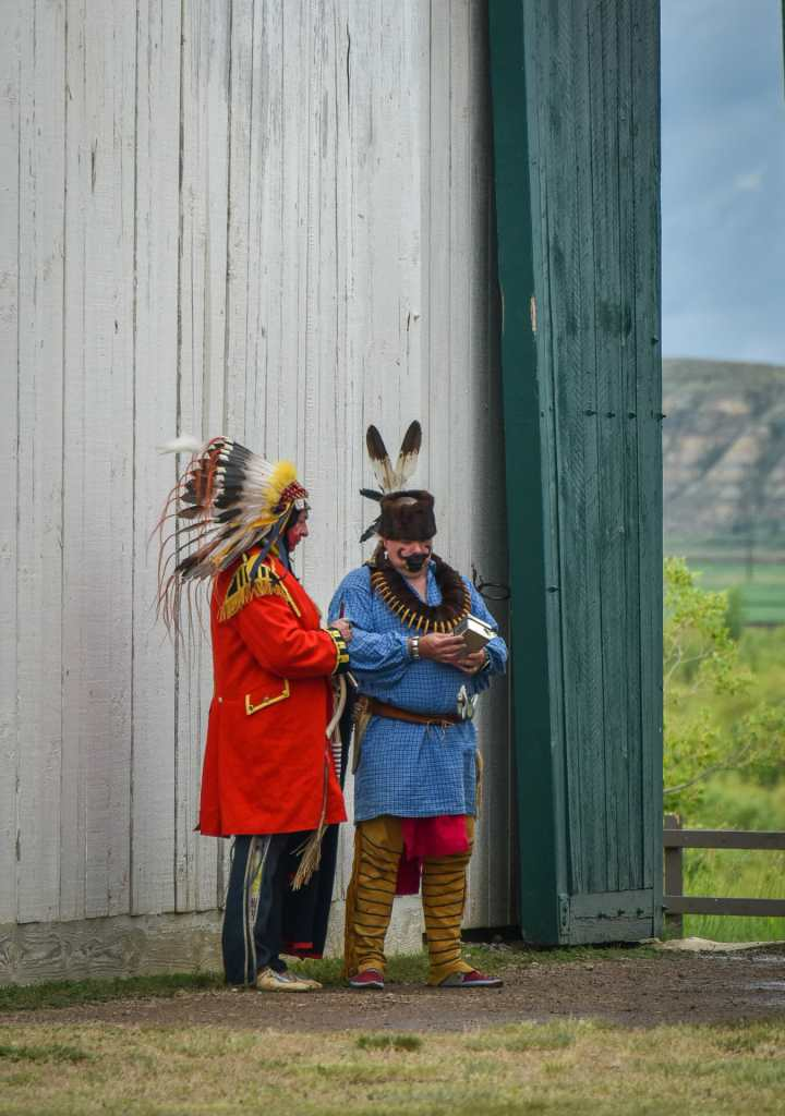 Two Native American re-enactors converse at gates of Fort Union Trading Post