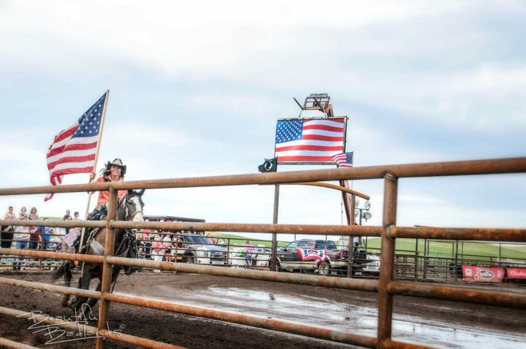 Miss Rodeo ND carries the flag at Killdeer Mountain Roundup Rodeo