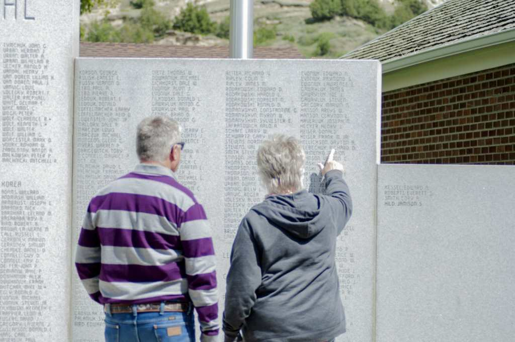 pointing out a name on the Medora veterans wall