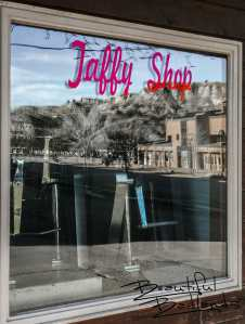 The Billings County Courthouse and the Bad Lands Motel are reflected in the window of the Taffy Shop in Medora, North Dakota.