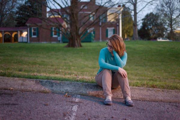 girl sitting on curb