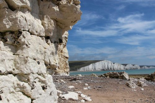 Overhanging chalk cliffs and Seven Sisters, beach, Hope Gap