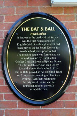 Sign on the wall of The Bat & Ball Inn, Hambledon