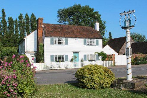 White clapboard cottage and The Biddenden Maids Village Sign, Biddenden