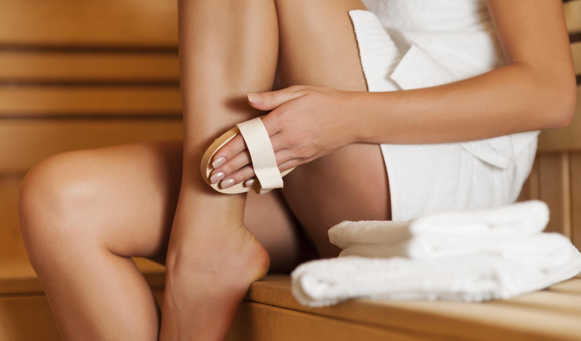 Woman massaging leg in sauna