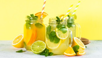 Lemonade set. Lemonade, mojito and orange lemonade. Iced summer drink in mason jar with ingredients. Bright yellow background.