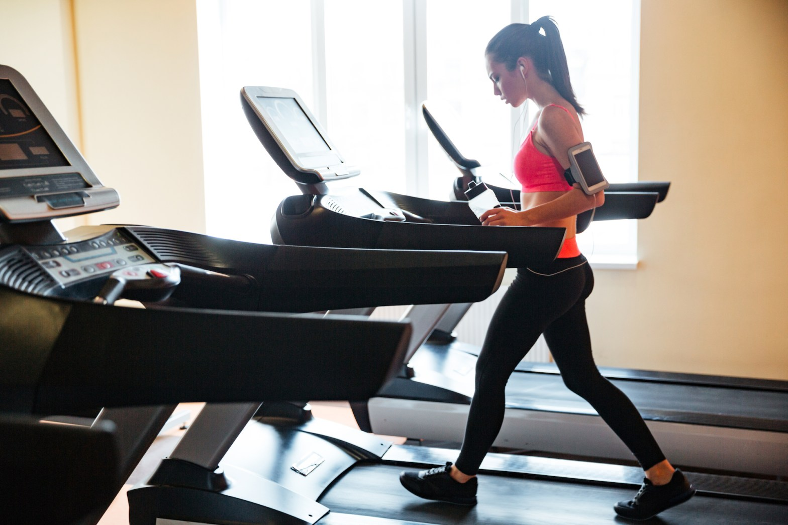 Sportswoman with earphones and blank screen smartphone using treadmill