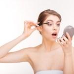 Charming woman applying mascara on her eyelashes isolated on a white background