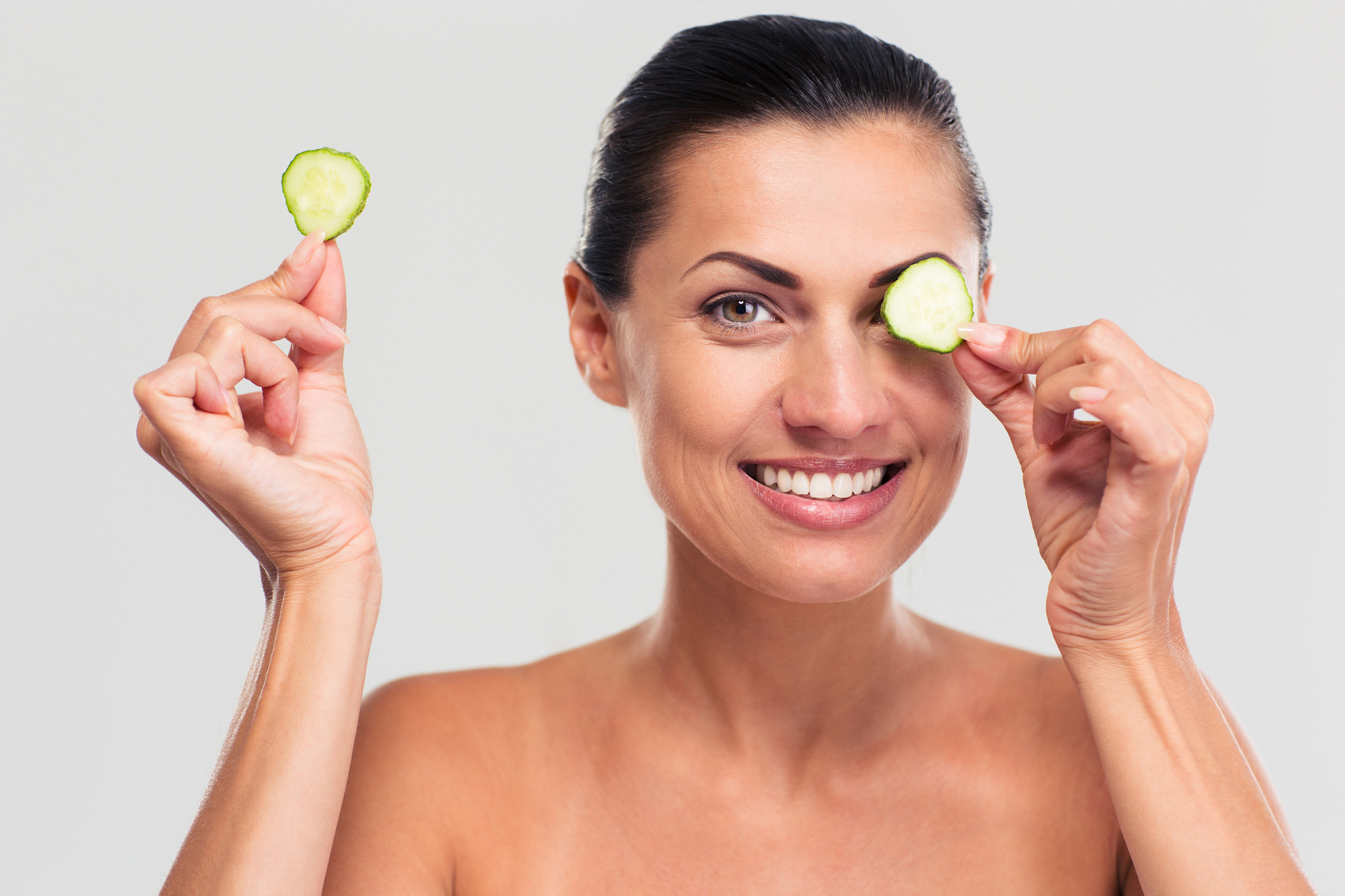 Happy woman covering her eye with cucumber
