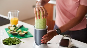 Close Up Of Woman Making Healthy Juice Drink With Fresh Ingredients In Electric Juicer After Exercise