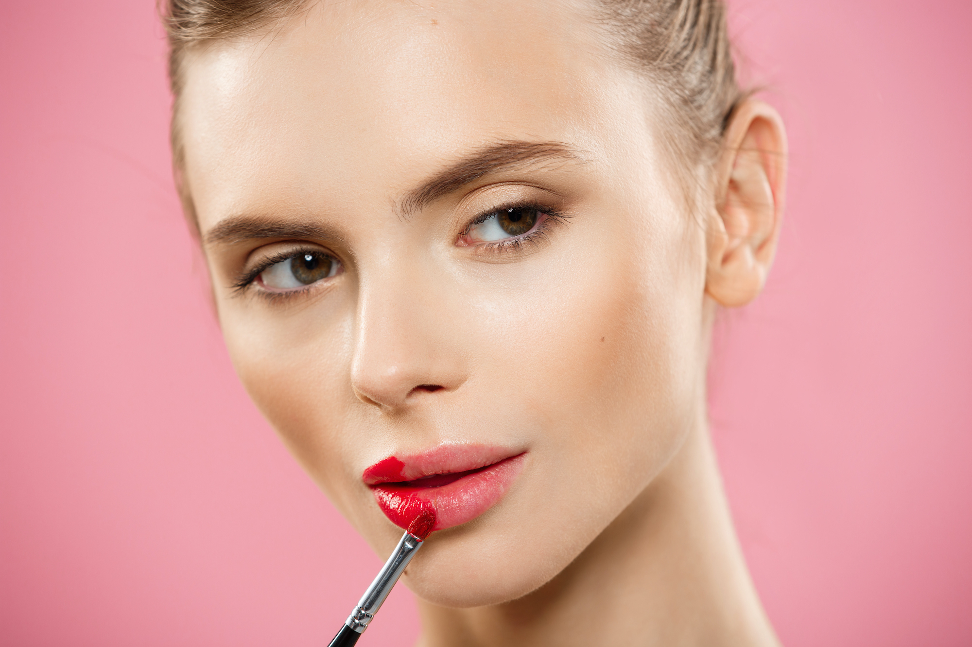 Beauty Concept – Woman applying red lipstick with pink studio background. Beautiful girl makes makeup.