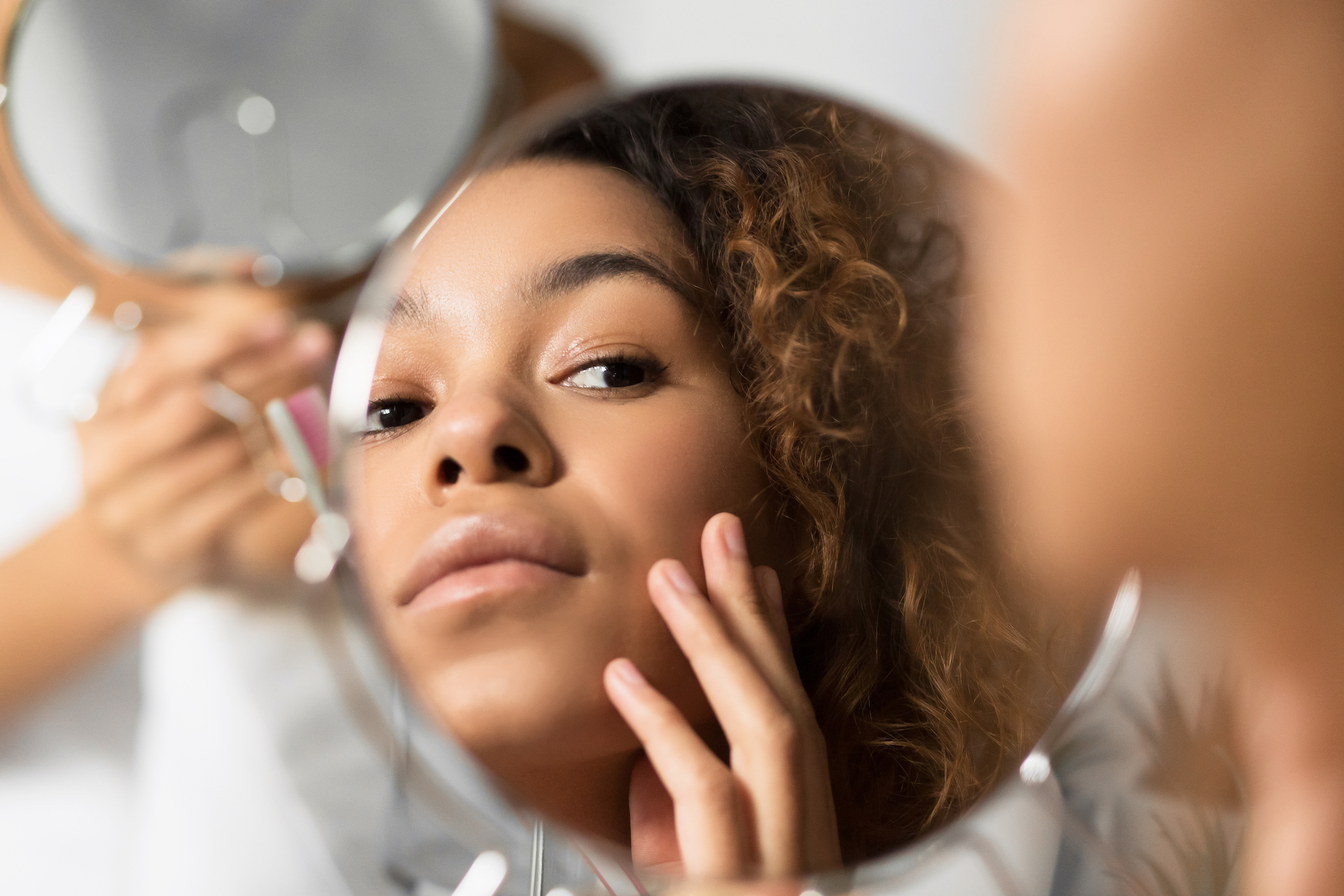 Skincare Concept. Afro Woman Looking In Mirror Touching Face And Perfect Skin At Bathroom. Selective Focus