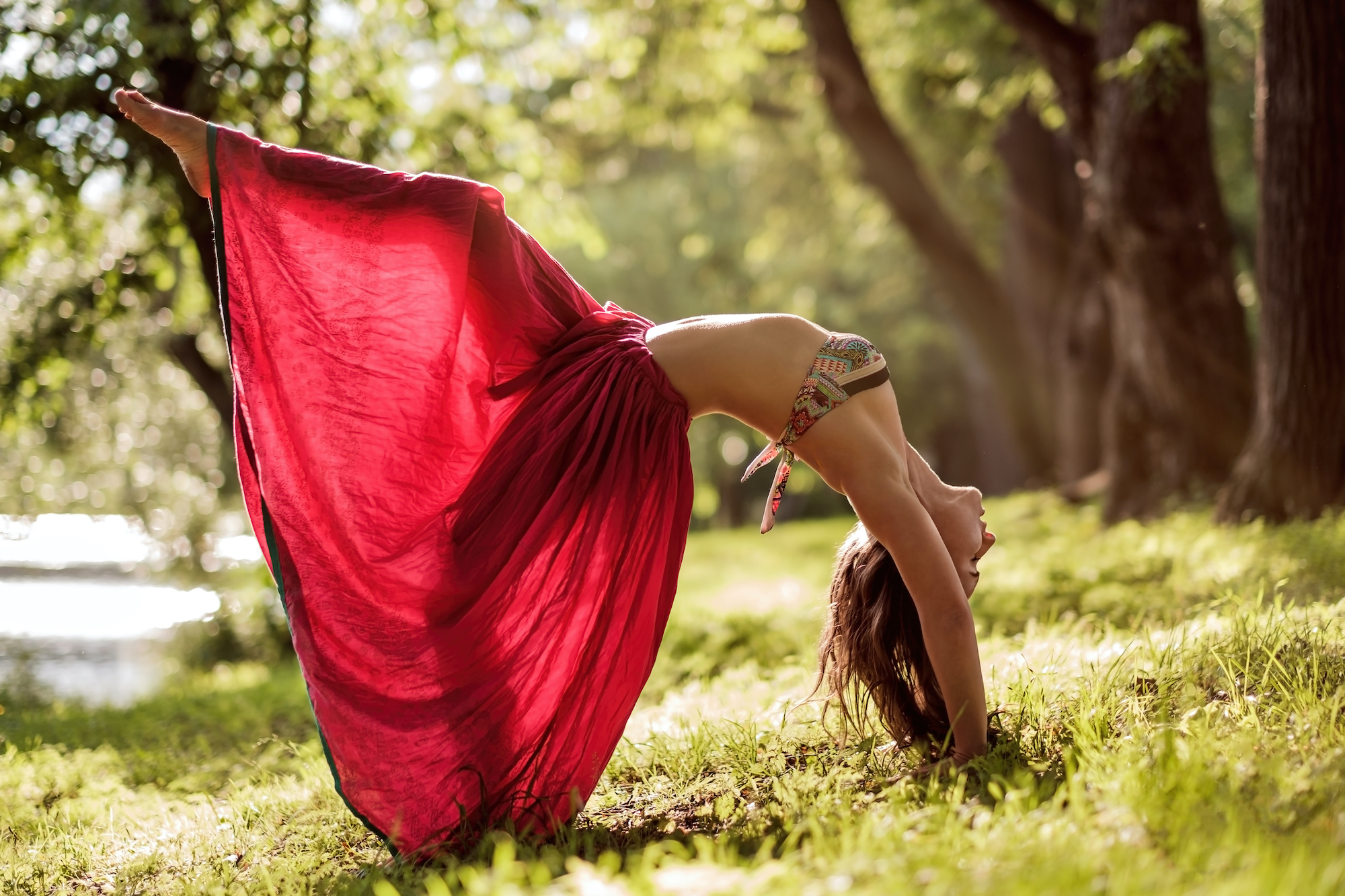 Fit young beautiful woman wearing red skirt working out outdoors in park on summer day, doing Bridge Pose, Urdhva Dhanurasana Upward Bow , Chakrasana Wheel from yoga