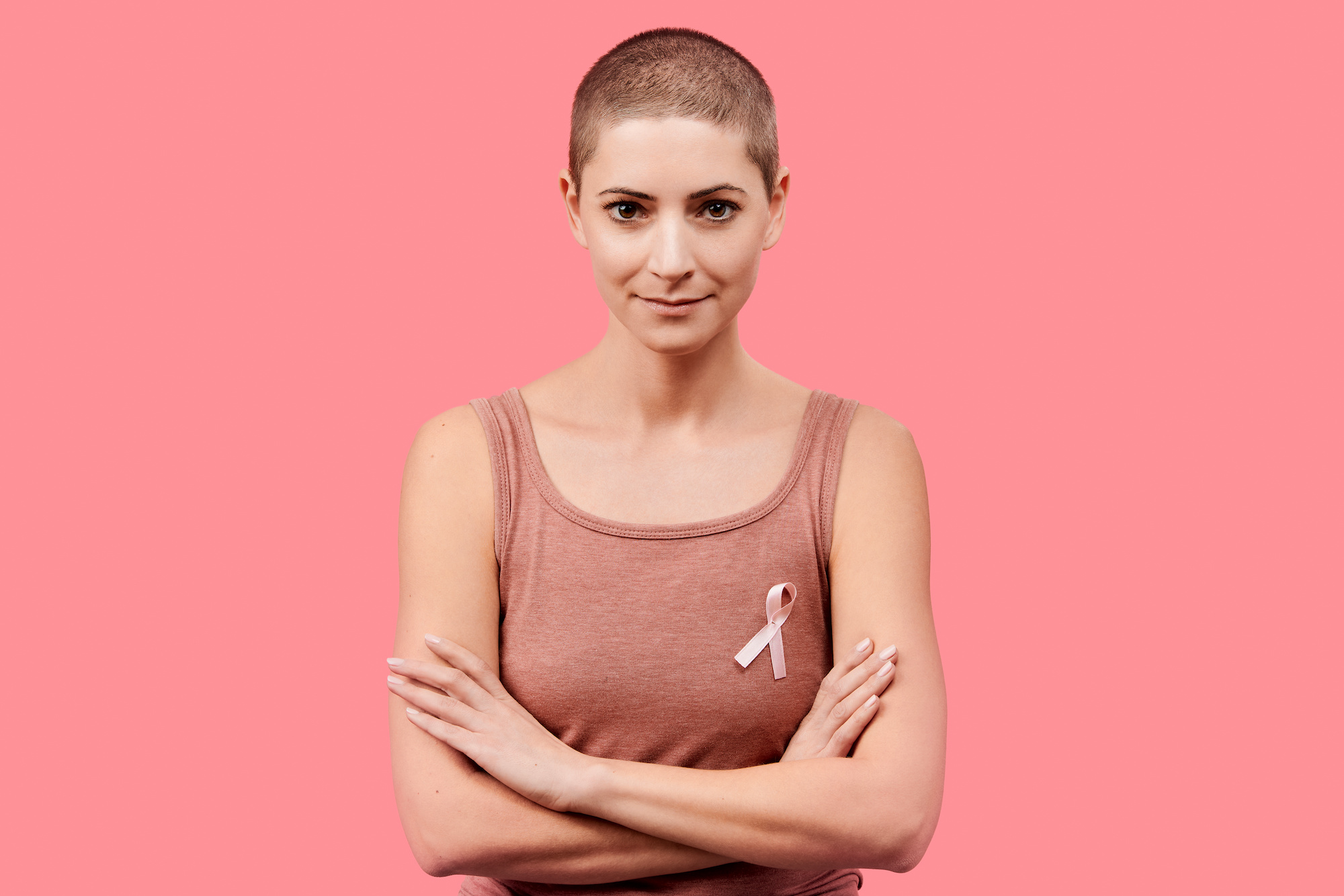 Smiling mid 30s woman, a cancer survivor, wearing pink breast cancer awareness ribbon, isolated over living coral background. Support, solidarity, screening and prevention concept.