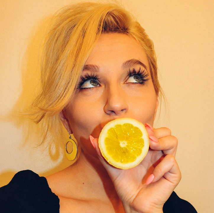 Woman Holding Lemon for DIY Hair Rinses