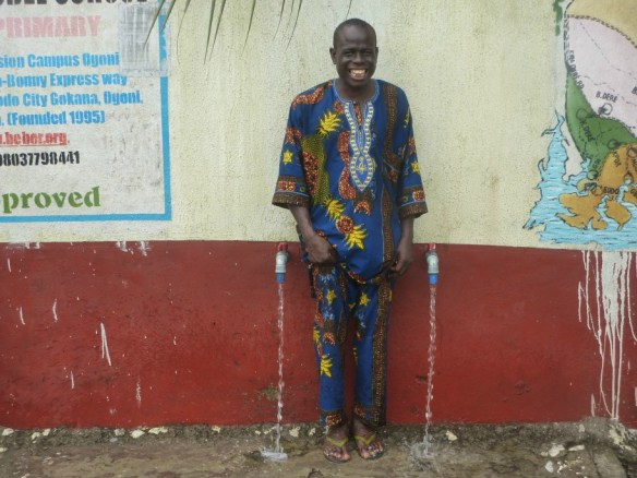 Reverend Moses Nyimale Lezor, the school director in Bodo standing between our two public water taps outside the school that enable local farmers and villagers to freely collect water from our borehole.