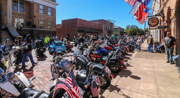 Hundreds of motorcyles parked on display on a cobblestone street