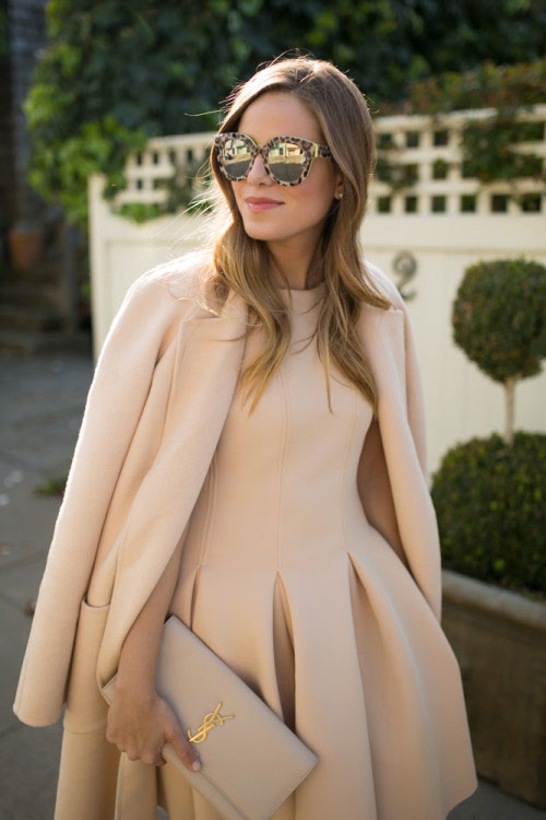 30 Chic Work Outfits to Wear this Summer: Fashion blogger 'Gal Meets Glam' wearing beige coat, a beige fit and flare midi dress, brown round sunglasses and a beige clutch. Work outfits, summer work outfits, office wear, business casual, fashion, street style, womens fashion.