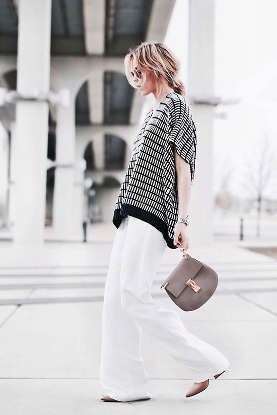 30 Chic Work Outfits to Wear this Summer: Fashion blogger 'Happily grey' wearing a black pattern poncho, white wide leg pants, nude block heel pumps, mirror sunglasses and a grey saddle bag. Work outfits, summer work outfits, office wear, business casual, fashion, street style, womens fashion.