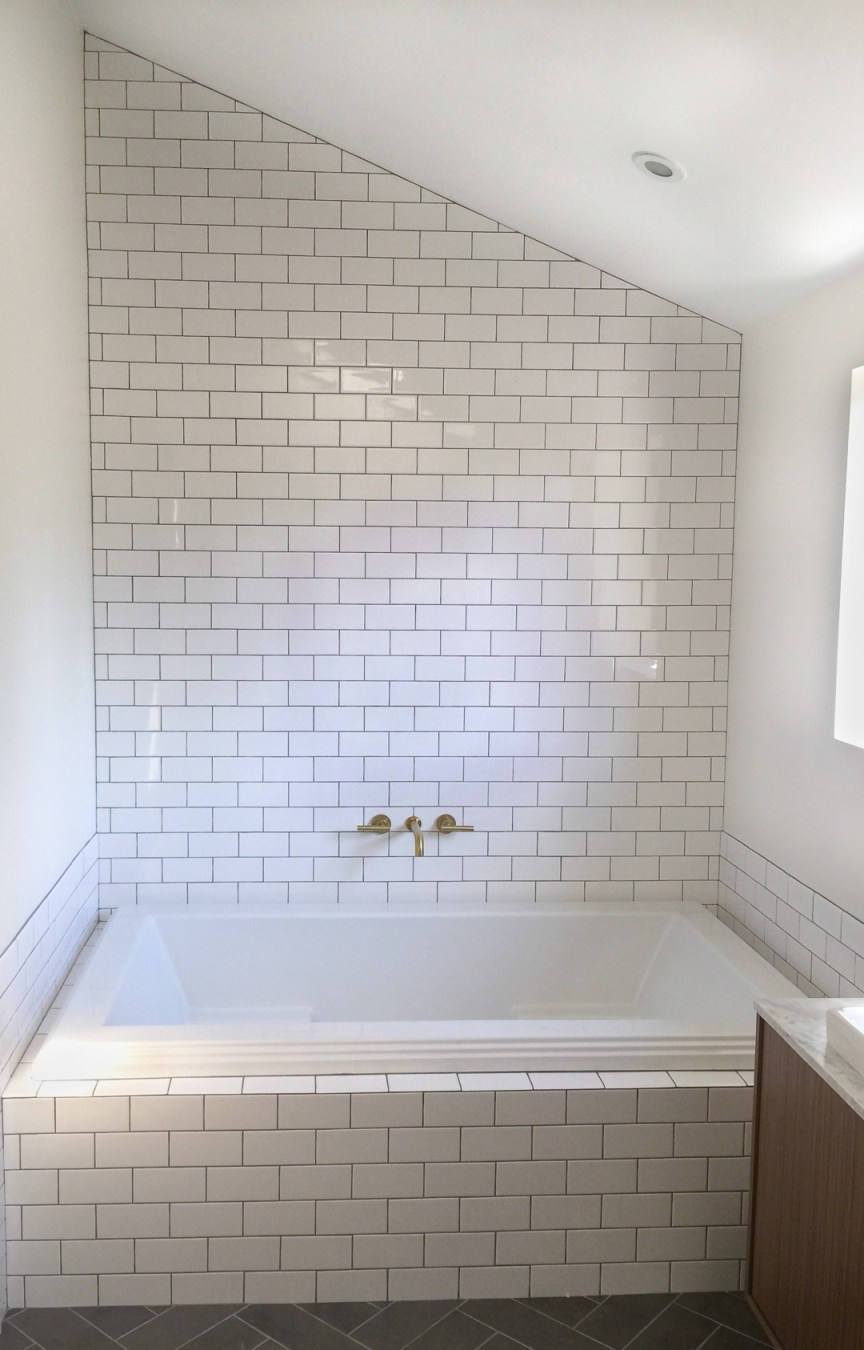 Master bathroom remodel with soaker tub, white subway tile with gray grout, brass wall mount faucet, and floating wood vanity by Beebout Design.