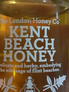 London Honey Company. Honey in contained in a bonta jar. Manifestation to glass. Plastic labels with white text.