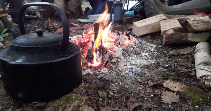 Storytelling around a campfire and kettle