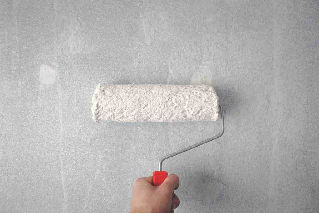 white paint brush going down a white wall