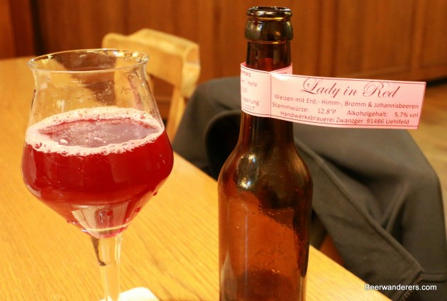 pink beer in glass with bottle