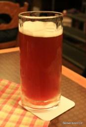 unfiltered dark amber beer in mug