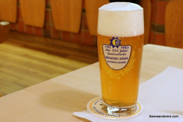 yellow beer in glass with big head