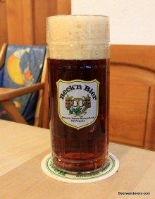 dark amber beer with huge head in mug