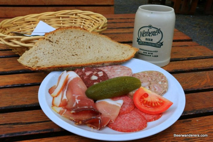 cold cuts on plate with bread and beer