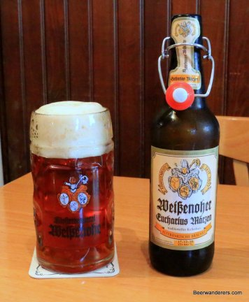 amber beer in mug with glass