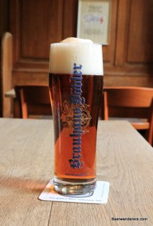 amber beer in glass with big head