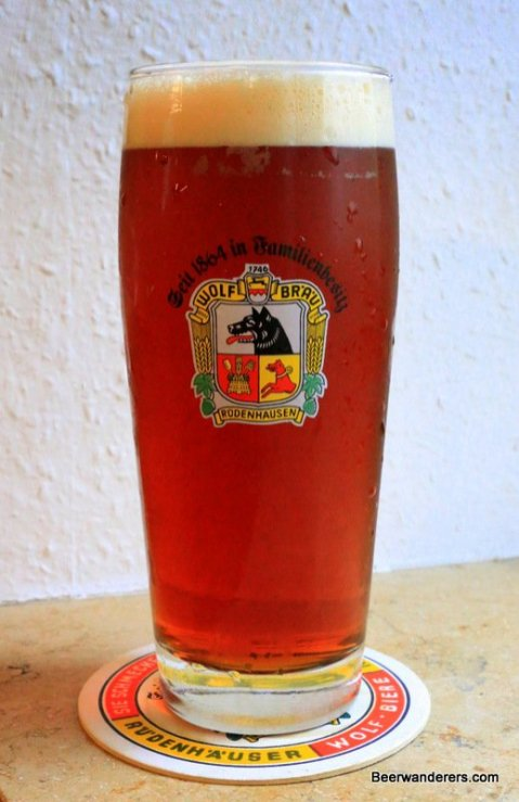 light brown beer in glass with logo