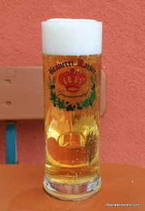 yellow beer in tall mug with logo