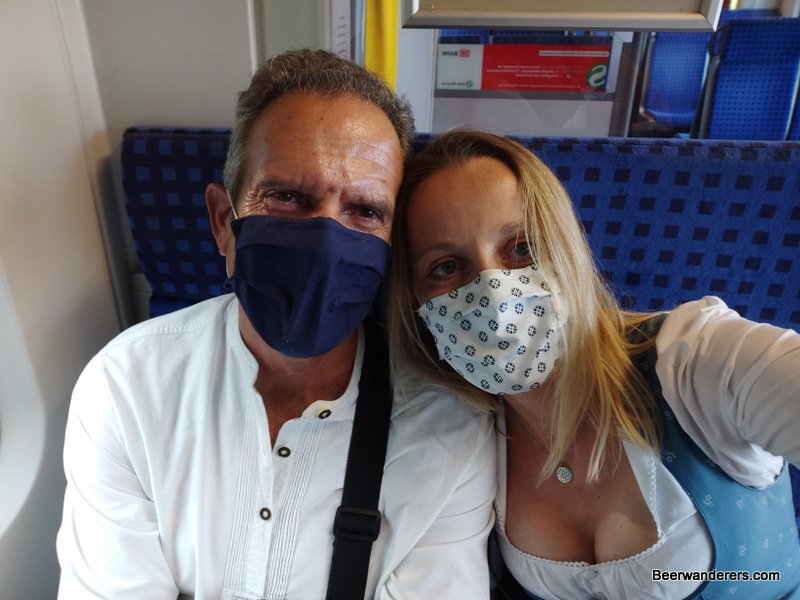 man and woman with masks in tracht