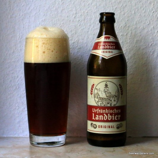 dark beer with big head in glass with bottle