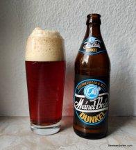 dark beer in glass with huge head and bottle