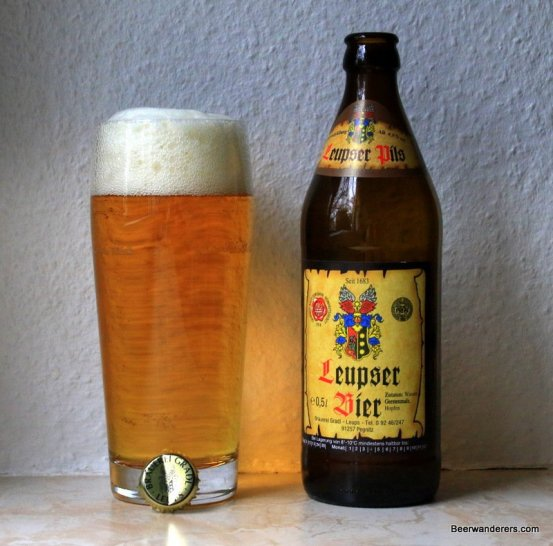 golden beer in glass with bottle