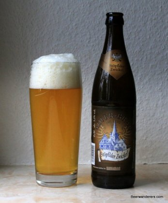 unfiltered yellow beer in glass with bottle