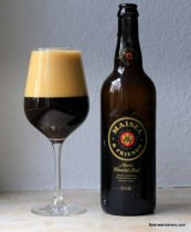 black beer in wine glass with bottle