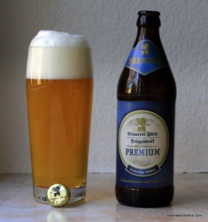 unfiltered golde beer with big head in glass with bottle