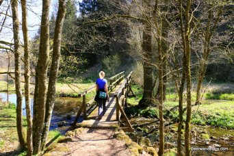 woman walking over small wooden bridge