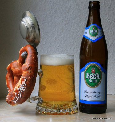 golden beer in clear mug with pewter lid and pretzel with bottle