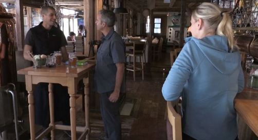 two guys talking at brewery with woman watching